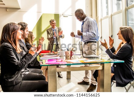 Business team having a meeting in a office, afro-american man exulting and his colleagues clapping hands - Successful businessman getting a promotion at work #1144156625