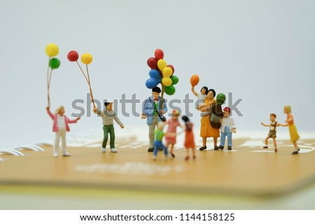 Miniature People : Family with colorful balloon stand on the book use as  and happy holiday concept. #1144158125