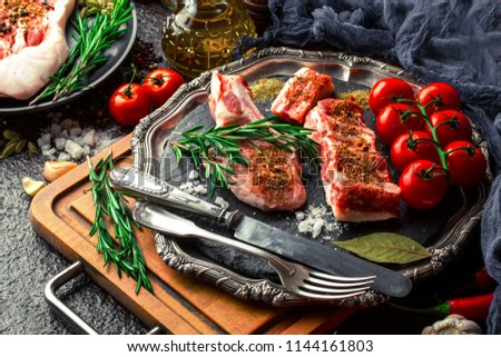 Raw meat on the kitchen table on a metallic background in a composition with cooking accessories #1144161803