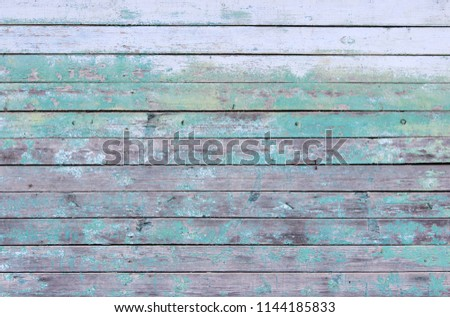 Vintage wood background with peeling turquoise old flaky paint. wall of an old house #1144185833