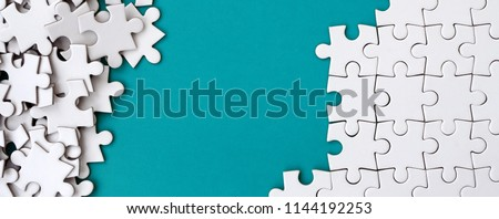 Fragment of a folded white jigsaw puzzle and a pile of uncombed puzzle elements against the background of a blue surface. Texture photo with space for text #1144192253