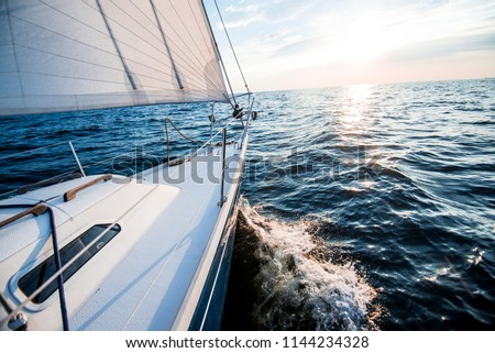 White sloop rigged yacht sailing at sunset. Top down view from of the deck, bow and sails. Baltic sea, Latvia. Transportation, nautical vessel, cruise, sport, regatta, recreation, leisure activity Royalty-Free Stock Photo #1144234328