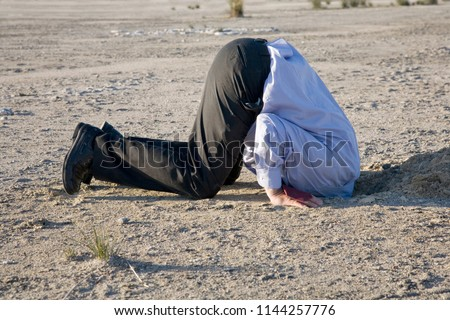 A powerful denial concept, man with his head in the sand. Royalty-Free Stock Photo #1144257776