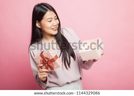 Young Asian woman open a gift box on pink background #1144329086