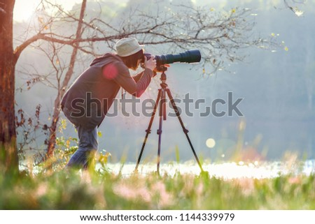 photographer taking photo with long telephoto fopr birds watching and animals, with lake forest and light beam dropped in background