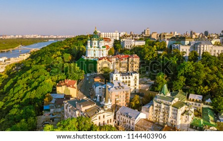 Aerial top view of Saint Andrew's church and Andreevska street from above, cityscape of Podol district on sunset, skyline of city of Kiev (Kyiv), Ukraine Royalty-Free Stock Photo #1144403906