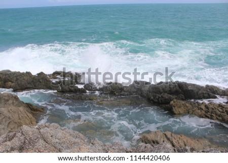 Waves crashing into rocks creating white water at Prom Thep Cape, Phuket, Thailand. #1144420406