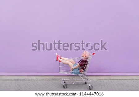 Young model poses with a cart on the background of a purple wall. Stylish girl with a shopping cart on a purple background.
