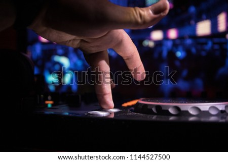 In selective focus of Pro dj controller.The DJ console deejay mixing desk at music party in nightclub with colored disco lights. Close up view #1144527500