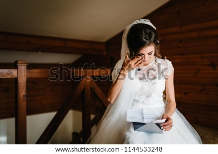 Beautiful bride reading letter from the groom for love. Bride's tears of happiness, joy. The bride sits at window and reads letter to groom. Wedding vows. Morning of the bride. Dress with lace. #1144533248