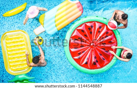 Happy friends playing with air lilo ball inside swimming pool - Young people having fun on summer holidays vacation - Travel, generation trends youth lifestyle, friendship and tropical concept #1144548887