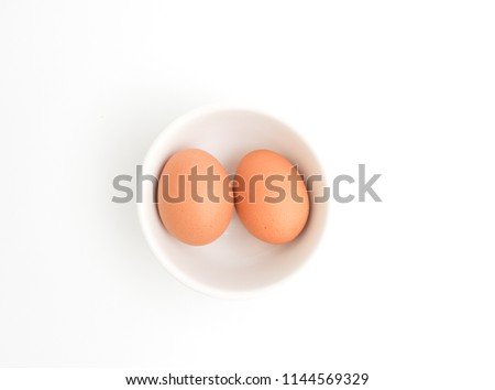 Two brown egg in white bowl and White background, isolated and top view picture.