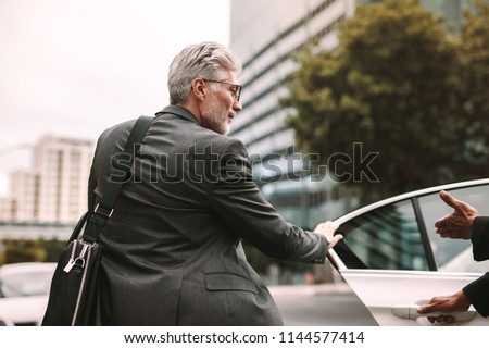 Mature businessman getting into a cab with driver opening door. Businessman entering a taxi on city street. #1144577414