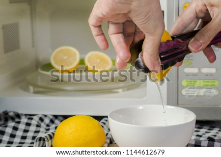 microwaving lemons for 20 - 30 seconds before squeeze make them soft and easily squeeze; use kitchen tongs help to squeeze;  kitchen tips #1144612679