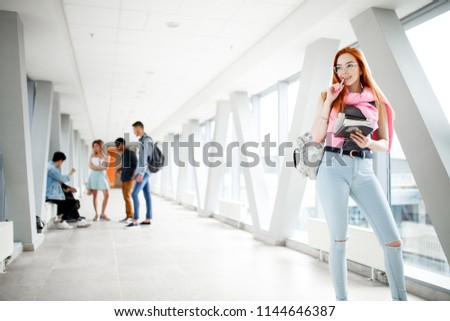 Young red-haired student at the University. A group of young students from different countries. The photo illustrates education, College, school, or University. #1144646387