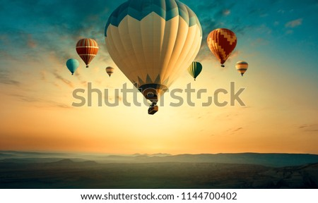 Panorama of Cappadocia skyline at sunrise - multicolored hot air balloons above mountains landscape. Goreme valley at sunset for your travel concept or horizontal billboard on Turkey in retro style. #1144700402