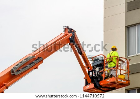 construction worker in yellow safety vest iworking on lifting hydraulic platform #1144710572