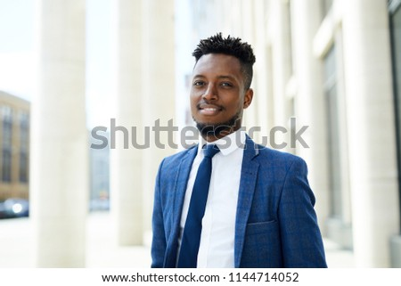 Happy young African-american employee in suit and tie looking at you in urban environment by modern business center #1144714052
