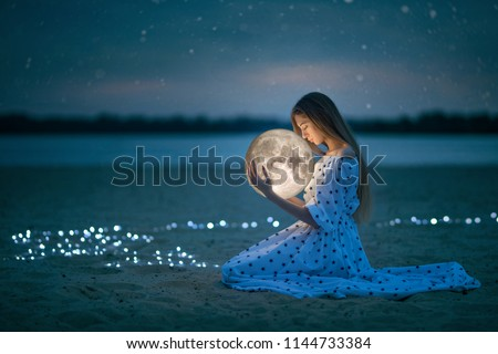 Beautiful attractive girl on a night beach with sand and stars hugs the moon, Artistic Photography #1144733384