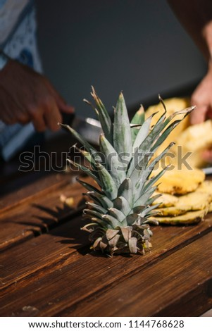 Man hands making pieces of a pineapple fruit. #1144768628