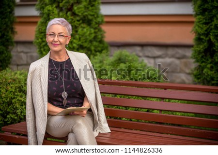 a businesswoman with white jacket on her shoulders in good mood looking at the camera. copy space #1144826336