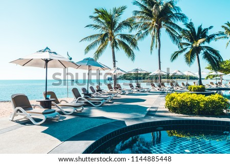 Beautiful tropical beach and sea with umbrella and chair around swimming pool in hotel resort for travel and vacation Royalty-Free Stock Photo #1144885448