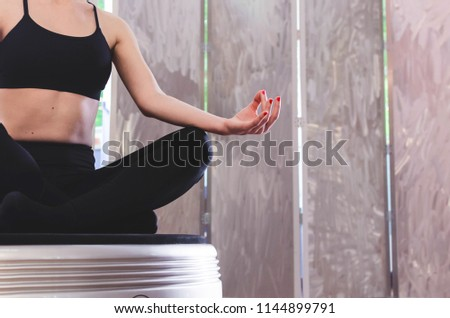 Cropped image of fit girl in yoga's lotos postion, at home on power plate, space for text. #1144899791