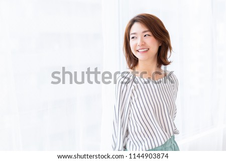 young attractive asian woman who opens a curtain #1144903874