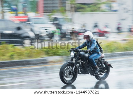 Nonthaburi, Thailand - July, 29, 2018 : Motion Blurred panning photo of Unidentified name people riding motorcycle in the rain on road at Nonthaburi, Thailand. #1144937621