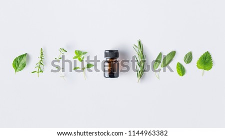 Bottle of essential oil with fresh herbs and spices basil, sage, rosemary, oregano, thyme, lemon balm  and peppermint setup with flat lay on white background #1144963382