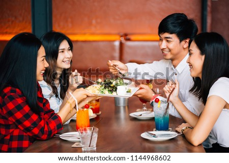 Group of Asian happy and smiling young man and women having a meal together with enjoyment and happiness #1144968602
