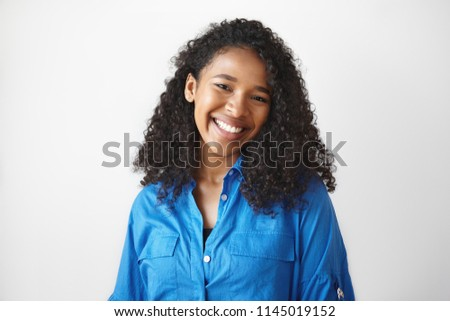 Picture of gorgeous African student girl wearing casual blue shirt rejoicing at good results on exams, smiling broadly. Beautiful young black woman looking at camera with charming cute smile #1145019152