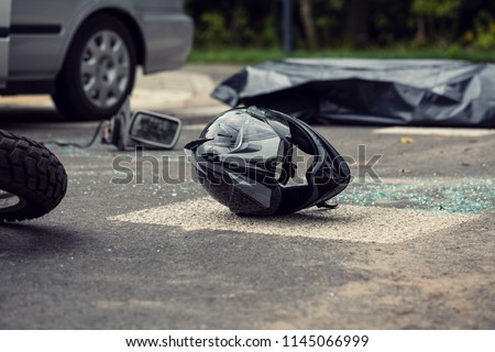 Black motorcycle helmet on the street after collision with a car Royalty-Free Stock Photo #1145066999
