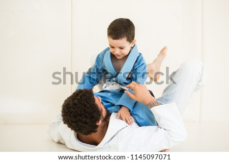 Father and little kid son are engaged in wrestling jiu-jitsu in the gym in a kimono. Trainer teaches child the methods and positions of single combat, karate or aikido. #1145097071