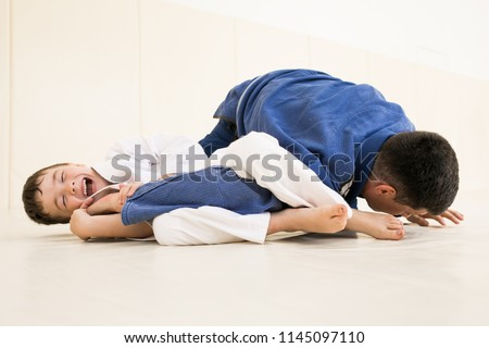Father and little kid son are engaged in wrestling jiu-jitsu in the gym in a kimono. Trainer teaches child the methods and positions of single combat, karate or aikido. Royalty-Free Stock Photo #1145097110