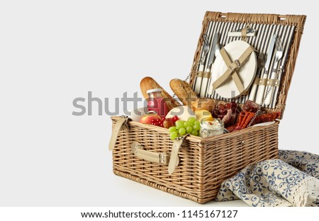 Picnic hamper packed with a tasty summer lunch with fresh fruit and juice, baguettes, spicy sausages and cheese isolated on white with copy space #1145167127
