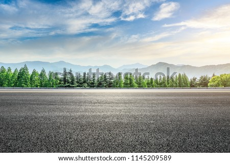 Asphalt road and forest with mountains scenery at sunrise #1145209589