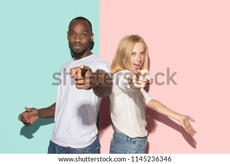 I choose you and order. The smiling mixed couple point you, want you, half length closeup portrait on studio background. The human emotions, facial expression concept. Front view. Trendy colors #1145236346