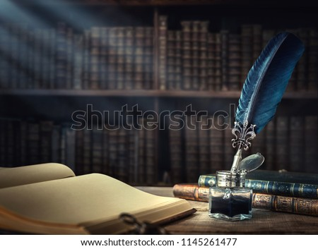 Old quill pen, books and vintage inkwell on wooden desk in the old office against the background of the bookcase and the rays of light. Conceptual background on history, education, literature topics. #1145261477