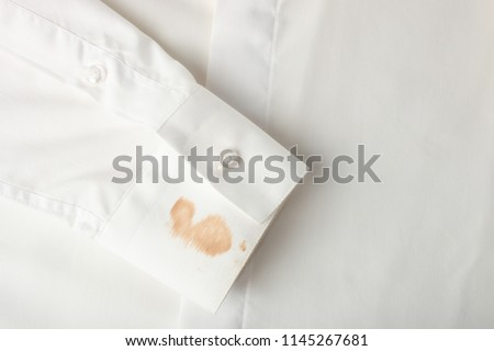 Dirty spot on the sleeve on white shirt. Concept stain remover. Top view. Royalty-Free Stock Photo #1145267681
