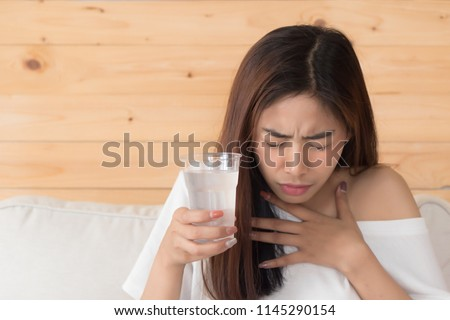 choking woman while drinking water; home danger, health insurance, choking hazard concept; young adult asian persian woman or asian middle east woman model #1145290154