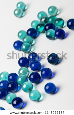 Multicolored glass balls scattered on a white background. Blue, green, transparent used in the interior. #1145299139