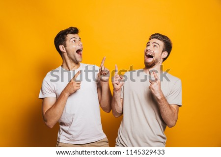 Portrait of a two excited young men best friends pointing fingers up at copy space isolated over yellow background