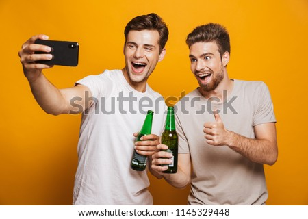 Portrait of a two cheerful young men best friends taking a selfie while holding beer bottles and shouting isolated over yellow background