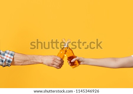 Close up cropped of woman and man two hands horizontal holding lager beer glass bottles and clinking isolated on yellow background. Sport fans cheer up. Friends leisure lifestyle concept. Copy space Royalty-Free Stock Photo #1145346926