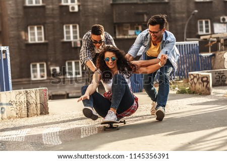 Group of friends hangout at the city street.Female sitting on skate board while friends pushing her from behind. #1145356391
