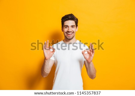 Portrait of handsome excited man in basic clothing smiling and showing ok sign at camera isolated over yellow background #1145357837