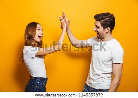 Image of friendly young people man and woman in basic clothing laughing and giving high five isolated over yellow background #1145357879