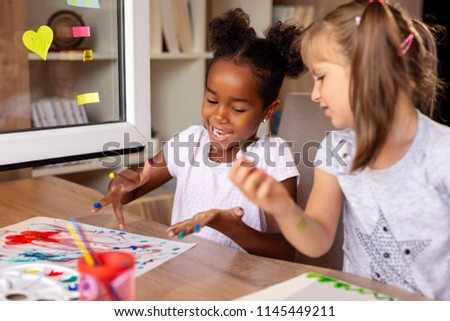 Beautiful little girls having fun painting with water colors, finishing their art class project #1145449211