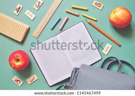 World Teachers' Day greeting card. Flat lay photo red apples, waffles, ruler, wooden cards with  numbers, crayons and a backpack on a green table. Back to school concept #1145467499